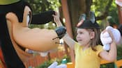 A girl wearing a Mouse ears hat goofs around with Goofy.