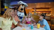 A family smiles at a table while Goofy laughs nearby in a chef costume