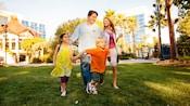 芝生の上を歩く家族