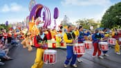 A parade with drummers, Pluto, and Mickey Mouse and Minnie Mouse on a float