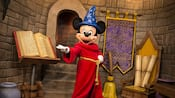 Mickey Mouse dressed as a wizard next to a brook, a book and scrolls