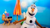 Olaf on a beach next to an umbrella and beach amenities
