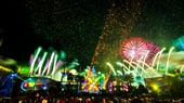 A fireworks and light show above a crowd