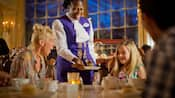 A waitress in a restaurant brings a chocolate dessert to a girl, with her surprised mother looking on