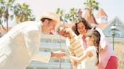 A man wearing a straw hat greets a little girl and her parents outside a hotel