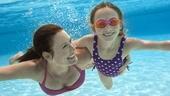 プールで泳ぐゴーグルをした母と娘