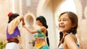 A girl laughs with delight as Aladdin and Jasmine dance