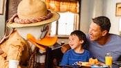 父と息子が朝食をとるテーブルを訪れたサファリルックのデイジー