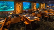 The inside of Coral Reef Restaurant with set tables, chairs and a glass tank filled with sharks and fish