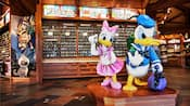 Statues of Donald Duck and Daisy Duck in a store with a sign saying Welcome Pin Traders