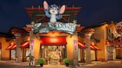 A statue of Stitch above the entrance to a store with a sign reading World of Disney