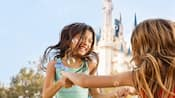 Two little girls play with bubbles in front of Cinderella Castle