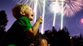 A boy sitting on his father's shoulders smiles while vibrant fireworks illuminate the evening sky