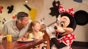 A smiling adult and child enjoying Character Dining with Minnie Mouse
