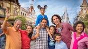 Una familia multigeneracional de 8 Visitantes parada en Main Street U.S.A., frente al castillo Cinderella Castle del Parque Magic Kingdom en Walt Disney World Resort