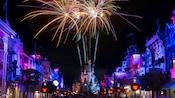 Los fuegos artificiales iluminan el cielo nocturno sobre Cinderella Castle al final de Main Street, USA, que luce decorado con luminosas linternas de Mickey Mouse