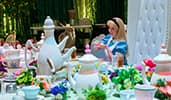 Alice from Alice in Wonderland sitting at a dining table decorated in a Mad Hatter Tea Party theme