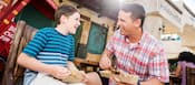 A father and son enjoy meat kebabs outside of the Harambe Market at Disney's Animal Kingdom theme park