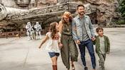 Une famille s'éloigne des stormtroopers du Premier Ordre et du Millennium Falcon