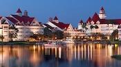Los botes que viajan en el agua frente a Disney's Grand Floridian Resort & Spa iluminan la noche