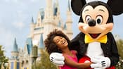 Mickey Mouse pasa un momento mágico con una niña frente al castillo de Cenicienta en el parque Magic Kingdom