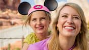 A mom and her young daughter, wearing a pink Mickey ear hat, enjoy a visit to Cars Land at Disney California Adventure Park