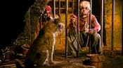Two jailed pirates beg a dog to bring them their cell key on the Pirates of the Caribbean attraction