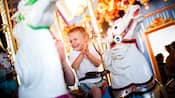 A boy claps while riding the King Arthur Carrousel