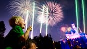 A smiling little boy looks at fireworks bursting in the sky near Sleeping Beauty Castle