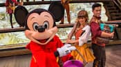Mickey Mouse holds a bucket of paint next to 2 helpers