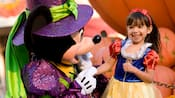 Minnie Mouse dressed as a witch next to a little girl