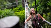 A young woman walks across a rope ladder in a rainforest