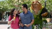 A woman with a glass of orange juice and her loving date near a topiary of Beast