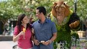 ビーストのトピアリーの近くでオレンジジュースを持って愛する人とデートをする女性