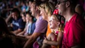 A little girl laughs at entertainment along with her parents and other audience members