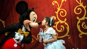 A girl dressed as a princess leans forward to kiss Mickey Mouse