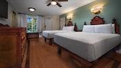 ベッドルームにある2つのキングベッド、ドレッサー、テレビ