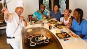 シェフが食べ物の横でミッキーフェイスを描く日本の鉄板焼きで食事をする家族