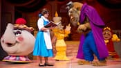 Performers acting as Belle, Beast, Mrs Potts, Lumiere and Cogsworth on stage