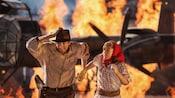 インディ・ジョーンズとマリオン・レイヴンウッドを演じるパフォーマーが燃える飛行機から逃げる