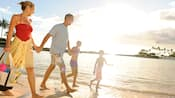 A man, woman, son and daughter walking by the water on a tropical beach