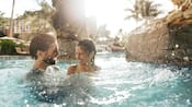 A father and daughter playing in an outdoor swimming pool at Aulani Resort