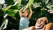 A smiling toddler, standing next to a menehune statue, pulls a large taro leaf on top of her head.