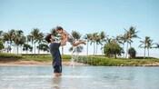 ヤシの木が植えられたビーチのそばのラグーンで、小さな男の子を高く抱え上げている父親