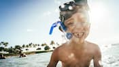 A smiling young boy in shallow ocean water, his snorkeling mask worn high on his forehead