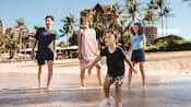 A family of 4 looks toward the ocean as they walk in the shallow water on the beach at Aulani Resort