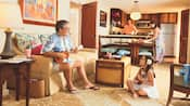 In an open living room, a grandfather and granddaughter play ukuleles while a couple prepares food