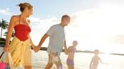 笑顔でコオリナ・ビーチを歩く 4 人の家族
