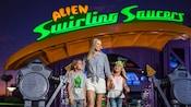 Una mujer y 2 niños parados frente a Alien Swirling Saucers