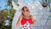 A young girl in a Minnie Mouse bathing suit screams in delight as she's showered with droplets of water in front of a structure that looks like it's made out of snow bricks